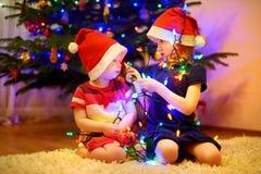 2 маленьких сестры украшая рождественскую елку Стоковая Фотография