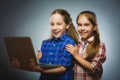 2 маленьких счастливых девушки используя компьтер-книжку изолировали серую предпосылку Стоковое Фото
