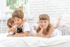 3 маленьких счастливых дет играя на кровати дома Стоковые Изображения RF