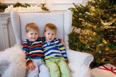 2 маленьких усмехаясь дет, мальчики близнецов сидя около рождественской елки Счастливые дружелюбные дети Стоковые Изображения RF