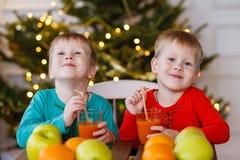 2 маленьких усмехаясь дет, мальчики выпивают фруктовый сок на предпосылке рождественской елки Счастливые дружелюбные дети Стоковая Фотография RF