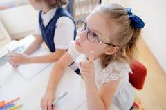 2 маленьких ученика начальной школы сидят на столе стоковое изображение rf