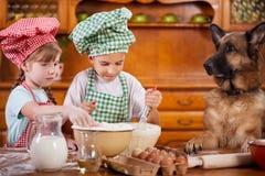 2 маленьких шеф-повара наслаждаясь в кухне делая большой беспорядок немецко Стоковая Фотография