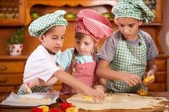 2 маленьких шеф-повара наслаждаясь в кухне делая большой беспорядок Стоковое Изображение RF