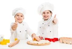 2 маленьких шеф-повара режа тесто с большими пальцами руки вверх Стоковое Фото