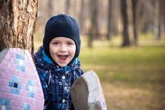 2 маленького ребенка играя, на ландшафте осени, положение и усмехаясь около большого дерева Стоковые Фотографии RF