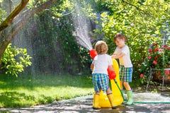 2 маленького ребенка играя с шлангом сада в лете Стоковое фото RF
