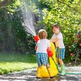 2 маленького ребенка играя с шлангом сада в лете Стоковое Фото