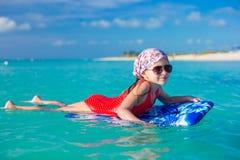 Маленькое милое заплывание девушки на surfboard в Стоковые Фотографии RF