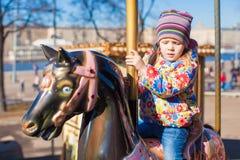 Маленькое счастливое катание девушки на carousel на парке атракционов Стоковые Изображения
