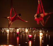 2 маленькой девочки в красном цвете выполняя воздушную йогу в расслабляющей свече освещают Стоковые Изображения