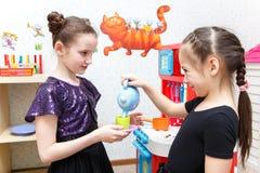 2 маленькой девочки играют игру роли с кухней игрушки в cen амбулаторного учреждения Стоковая Фотография