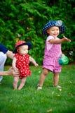 2 маленькой девочки играя на зеленой траве весной садовничают стоковое фото rf