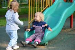 2 маленькой девочки играя на спортивной площадке Стоковое фото RF