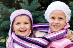 2 маленькой девочки обнимая около рождественской елки Стоковые Изображения RF