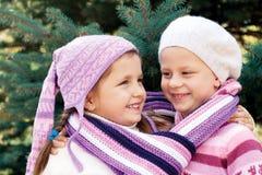 2 маленькой девочки обнимая около рождественской елки Стоковые Фото