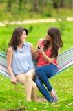 2 маленькой девочки отдыхая на усмехаться гамака Стоковые Фотографии RF
