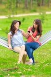 2 маленькой девочки отдыхая на усмехаться гамака Стоковые Изображения