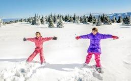 2 маленькой девочки падая и имея потеху на снеге Стоковые Изображения