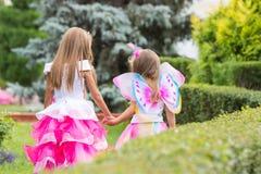 2 маленькой девочки, принцесса и фея, руки прогулки в саде Стоковое Изображение