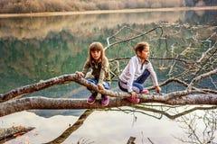 2 маленькой девочки сидя на дереве на озере Biogad (Biogradsko Стоковые Фотографии RF