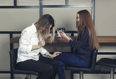 2 маленькой девочки счастливы и смеющся над пока один из смотреть в smartphone на счетчике в кафе Стоковое Изображение