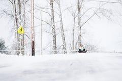 2 маленькой девочки sledding вниз с холма в льде и снеге Стоковые Фотографии RF