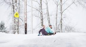 2 маленькой девочки sledding вниз с холма в льде и снеге Стоковая Фотография