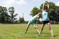 2 маленькой девочки stetching перед jogging Стоковая Фотография