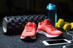 Малиновые тапки ` s женщин, желтые гантели, бутылка и белый мобильный телефон с наушниками на запачканной предпосылке Стоковые Фотографии RF