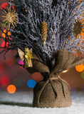 Малое дерево Xmas таблицы стоя в снеге, с светами рождественской елки, предпосылкой bokeh и космосом экземпляра Стоковые Изображения RF