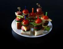 Малое канапе закусок с томатами вишни, cheeze, сосисками и овощами на хлебе на протыкальниках на белой плите Стоковые Изображения