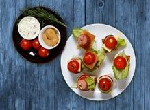 Малое канапе закусок с томатами вишни, cheeze, сосисками и овощами на хлебе на протыкальниках на белой плите с плитой соусов Стоковое Изображение RF