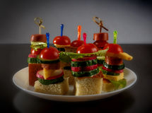 Малое канапе закусок с томатами вишни, cheeze, сосисками и овощами на хлебе на протыкальниках на белой плите Стоковое Фото