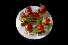 Малое канапе закусок с томатами вишни, cheeze, сосисками и овощами на хлебе на протыкальниках на белой плите Стоковая Фотография RF