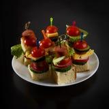 Малое канапе закусок с томатами вишни, cheeze, сосисками и овощами на хлебе на протыкальниках на белой плите Стоковые Изображения RF