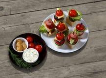 Малое канапе закусок с томатами вишни, cheeze, сосисками и овощами на хлебе на протыкальниках на белой плите с плитой соусов Стоковое фото RF