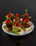 Малое канапе закусок с томатами вишни, cheeze, сосисками и овощами на хлебе на протыкальниках на белой плите Стоковое Изображение