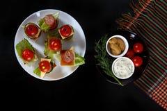 Малое канапе закусок с томатами вишни, cheeze, сосисками и овощами на хлебе на протыкальниках на белой плите с плитой соусов Стоковая Фотография