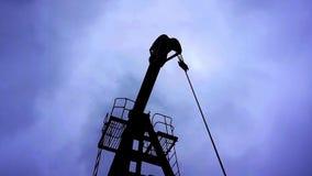 Малое частное масло насосов деррик-крана на драматическом небе с предпосылкой облаков сток-видео