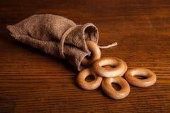 Малые бейгл в сумке на деревянной предпосылке Стоковое Фото