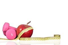 Малые гантели и яблоко для тренировки и метра Стоковое фото RF