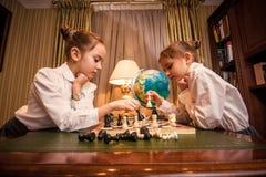 Малые девушки играя шахмат Стоковые Изображения