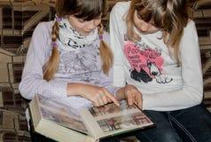 Малые девушки наблюдая семейные фото Стоковая Фотография