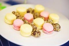 Малые десерты для гостей на плите Macaroons и малые торты Мягкий селективный фокус на тортах Стоковые Изображения RF