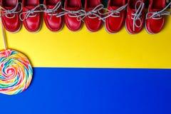 Малые красные ботинки шлюпки, леденец на палочке Стоковое Фото