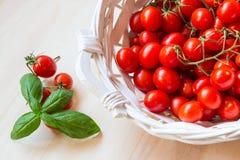 Малые красные томаты вишни в плетеной корзине на старом деревянном столе Стоковое фото RF