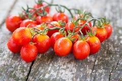 Малые красные томаты вишни на старом деревянном столе в деревенском стиле Стоковое фото RF