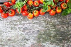 Малые красные томаты вишни на старом деревянном столе в деревенском стиле Стоковая Фотография RF