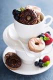 Малые мини donuts в штабелированных кофейных чашках Стоковая Фотография